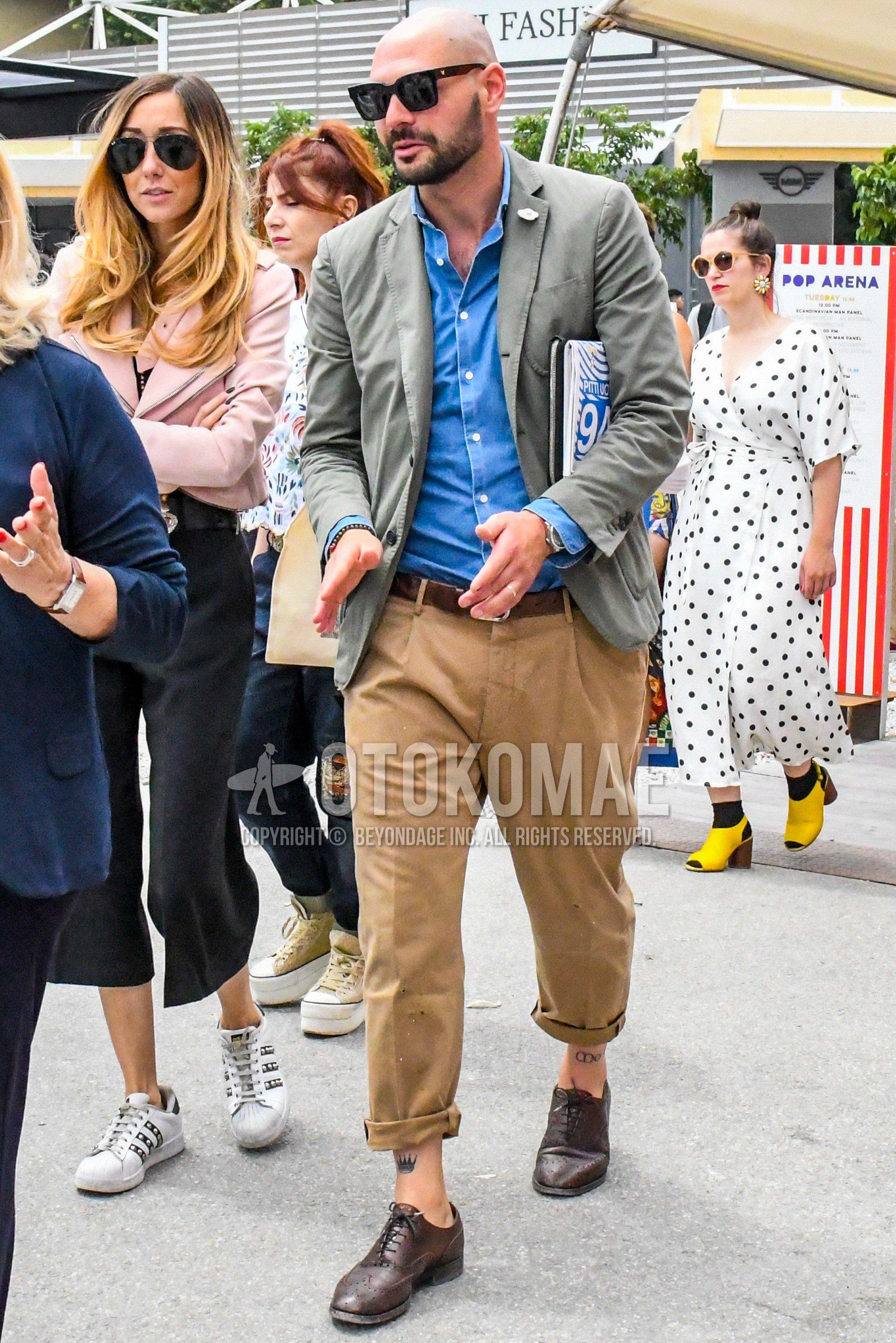 黒無地のサングラス、ラルディーニのグレー無地のテーラードジャケット、ブルー無地のデニム/シャンブレーシャツ、ブラウン無地のレザーベルト、ベージュ無地のチノパン、ブラウンウィングチップの革靴を合わせた春夏秋のメンズコーデ・着こなし。