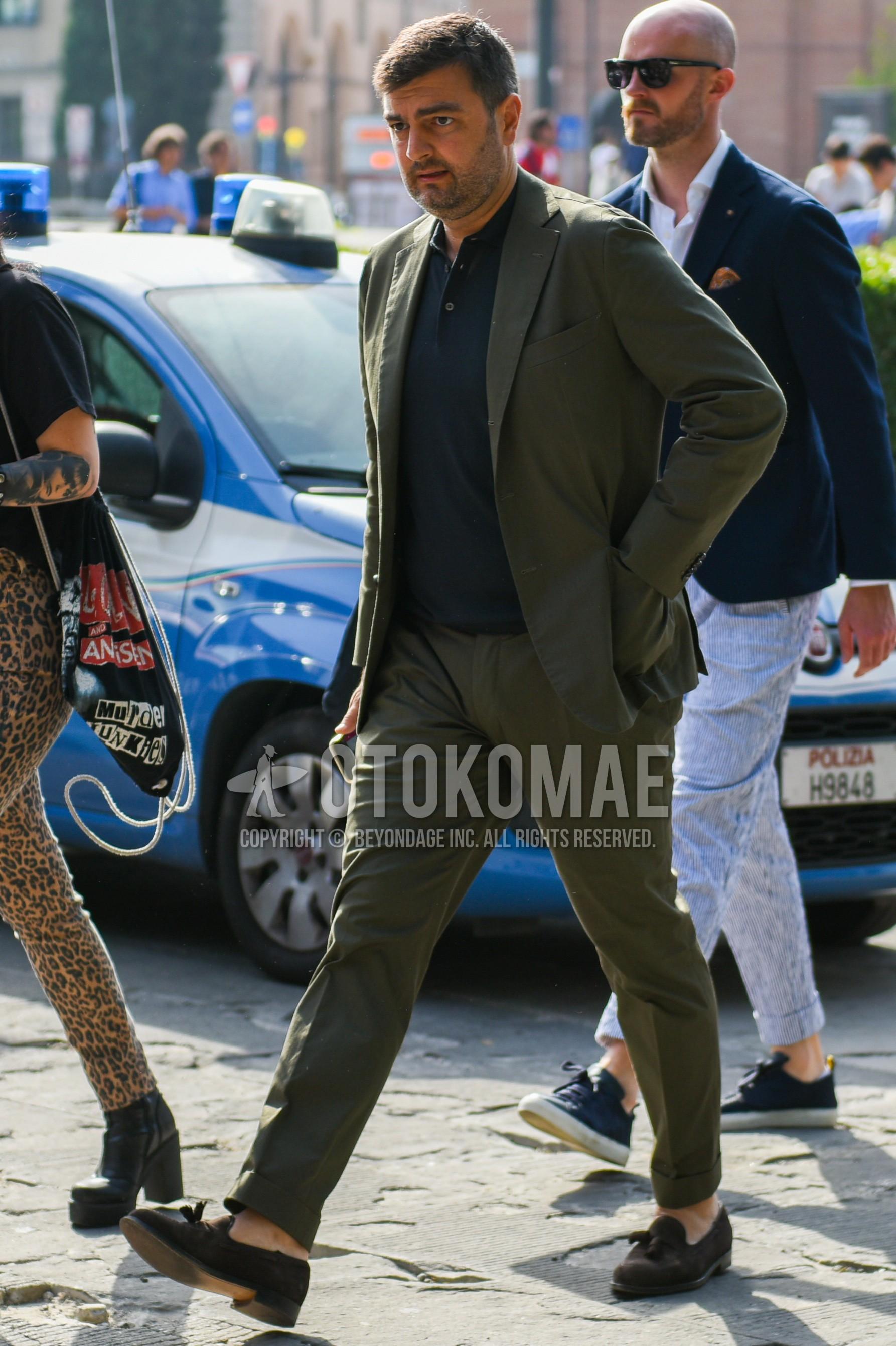 黒無地のポロシャツ、スエードのブラウンタッセルローファーの革靴、オリーブグリーン無地のスーツを合わせた春夏のメンズコーデ・着こなし。