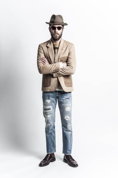 ダメージデニムのパンツにベージュのジャケットをあわせた着こなし