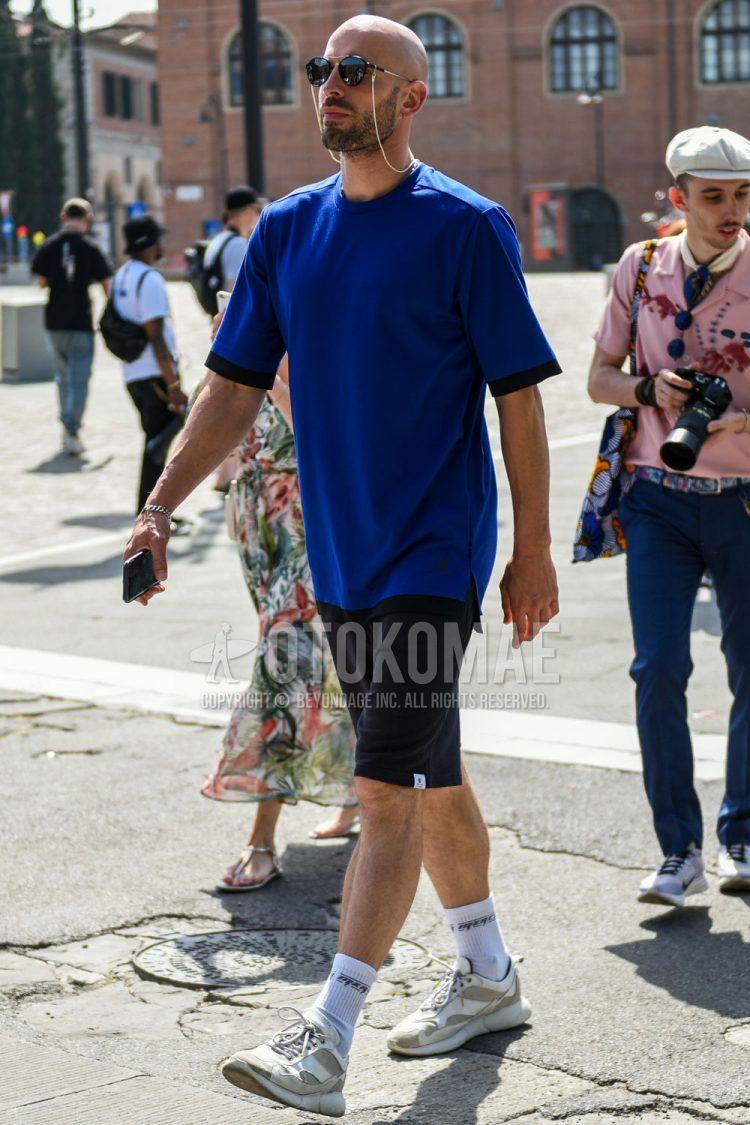 黒無地のサングラス、ブルー無地のTシャツ、黒無地のショートパンツ、白無地のソックス、白ローカットのスニーカーを合わせた夏のメンズコーデの着こなし。