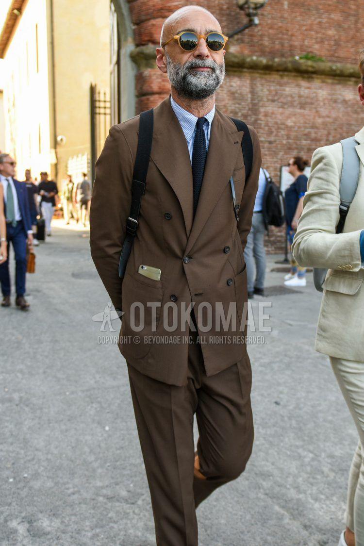 ベージュ無地のサングラス、ブルーストライプのシャツ、ブラウン無地のスーツ、ネイビー無地のニットタイを合わせた春秋のメンズコーデの着こなし。