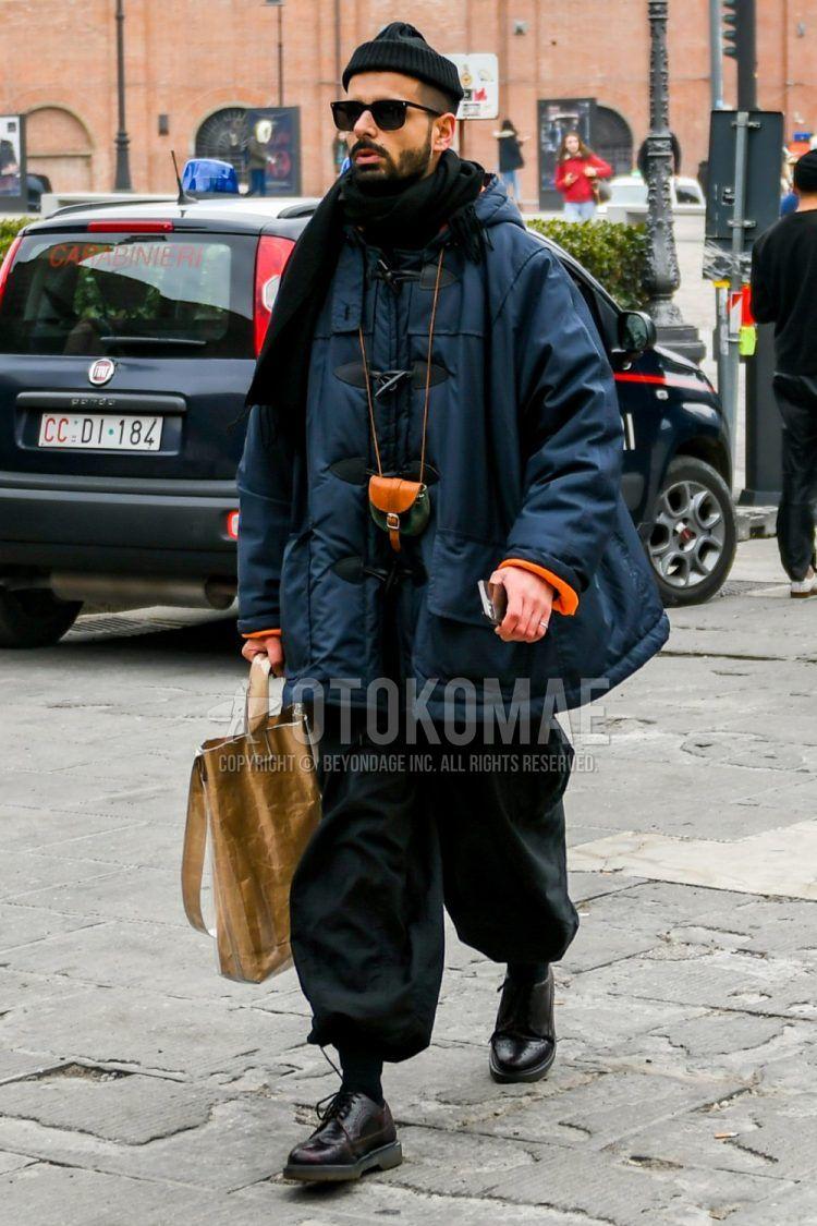 黒無地のニットキャップ、無地のサングラス、ネイビー無地のダッフルコート、黒無地のワイドパンツ、黒無地のソックス、黒ブローグシューズの革靴、ベージュ無地のトートバッグを合わせたメンズコーデ・着こなし。