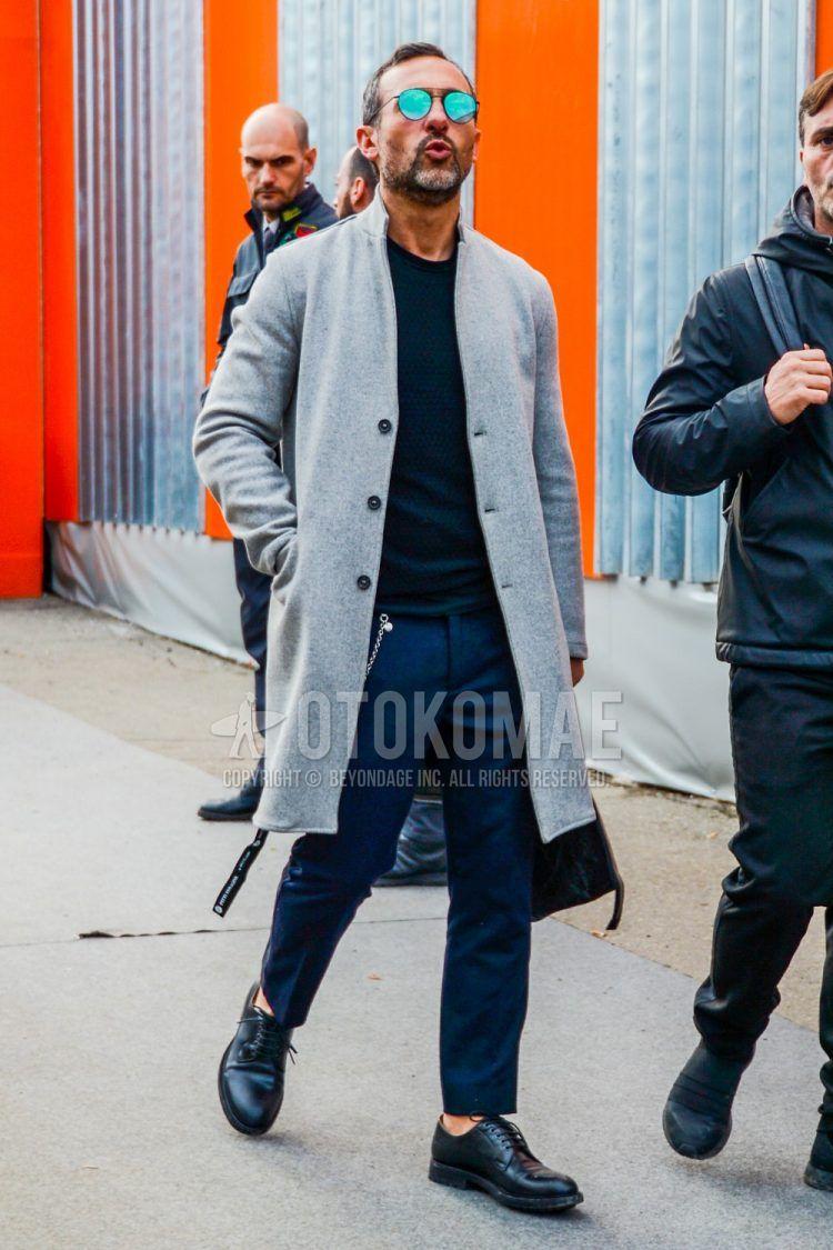 無地のサングラス、グレー無地のチェスターコート、黒無地のセーター、グレー無地のスラックス、黒プレーントゥの革靴を合わせたメンズコーデ・着こなし。