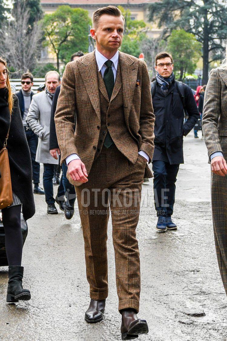白無地のシャツ、ブラウンサイドゴアのブーツ、ブラウンチェックのスリーピーススーツ、グリーン無地のネクタイを合わせたメンズコーデ・着こなし。