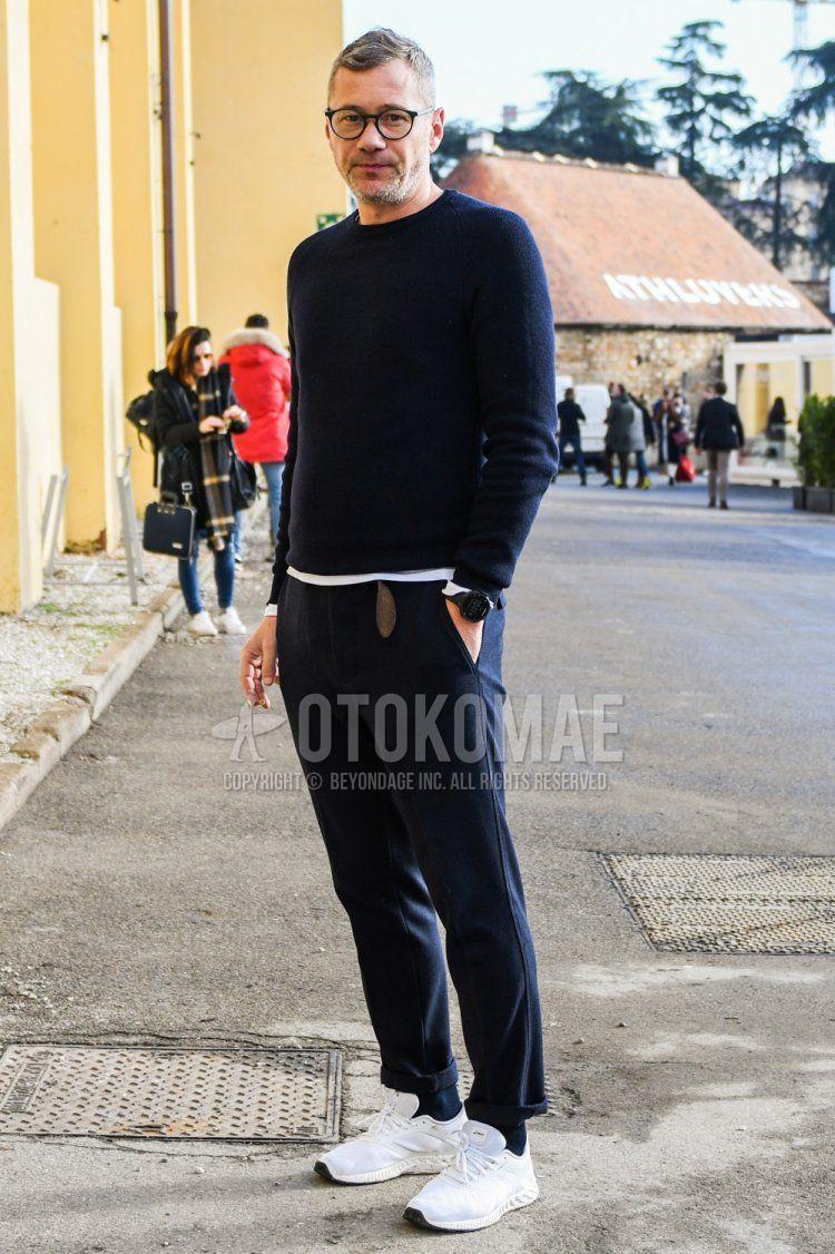ネイビー無地のセーター、白無地のTシャツ、ネイビー無地のコットンパンツ、ネイビー無地のソックス、白ローカットのスニーカーを合わせた春秋のメンズコーデ・着こなし。