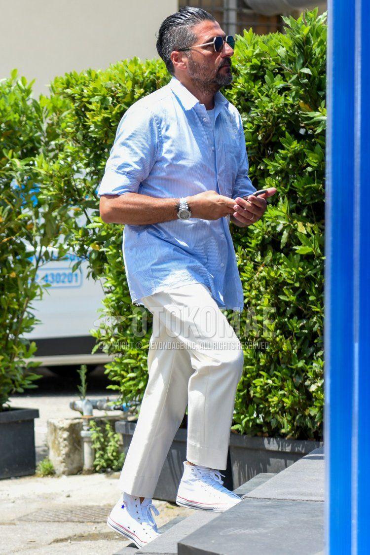 ゴールド・黒無地のサングラス、水色無地のシャツ、白無地のアンクルパンツ、コンバースの白ハイカットのスニーカーを合わせたメンズコーデ・着こなし。