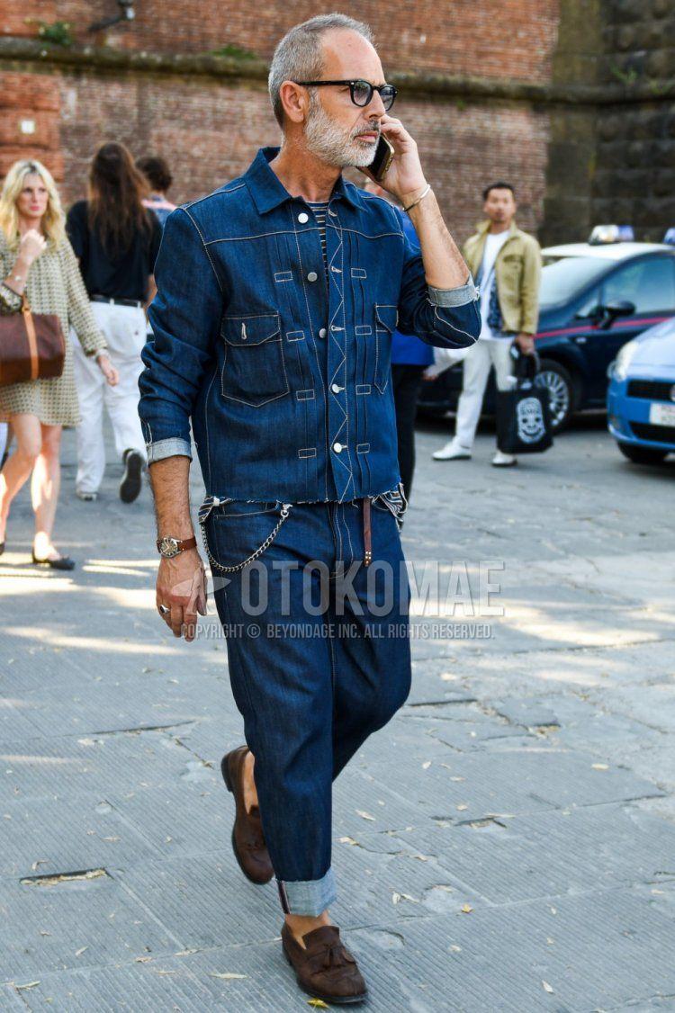 黒無地のサングラス、ブルー無地のデニムジャケット、ブルー・ブラウンボーダーのTシャツ、ブラウン無地のレザーベルト、ブルー無地のデニム/ジーンズ、スエードのブラウンタッセルローファーの革靴を合わせたメンズコーデ・着こなし。