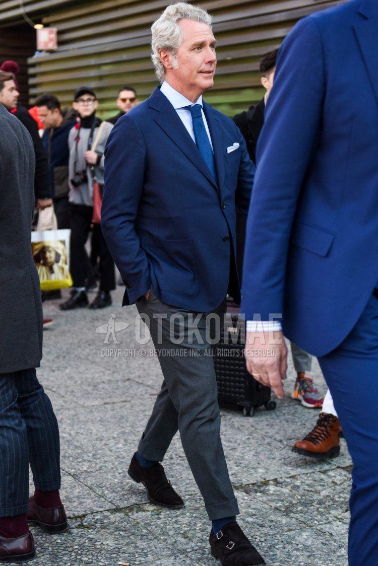 ネイビー無地のテーラードジャケット、白無地のシャツ、グレー無地のスラックス、グレー無地のアンクルパンツ、グレー無地のソックス、スエード のブラウンモンクシューズの革靴、ネイビー無地のネクタイを合わせた春秋のメンズコーデ・着こなし。
