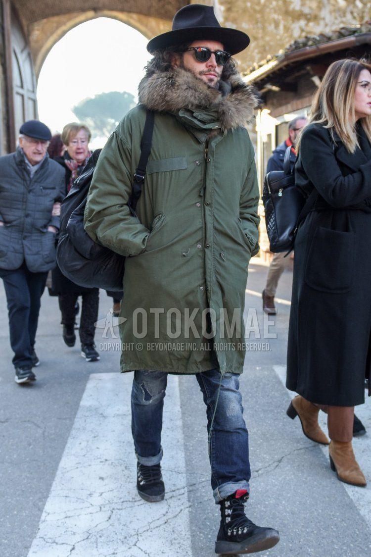 黒無地のハット、ボストンの黒無地のサングラス、オリーブグリーン無地のモッズコート、グレー無地のダメージジーンズ、黒のブーツを合わせた秋冬のメンズコーデ・着こなし。