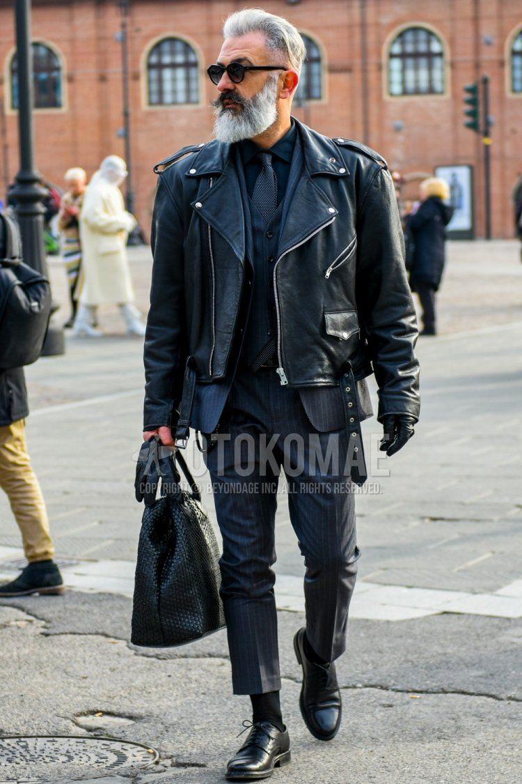 ラウンドの黒無地のサングラス、黒無地のライダースジャケット、黒無地のシャツ、黒無地のソックス、黒ストレートチップの革靴、黒無地のブリーフケース/ハンドバッグ、ネイビーストライプのスリーピーススーツ、黒無地のネクタイを合わせた冬のメンズコーデ・着こなし。