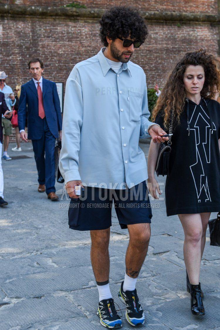 ウェリントンの黒無地のサングラス、水色無地のシャツ、ネイビー無地のショートパンツ、白無地のソックス、マルチカラーローカットのスニーカーを合わせた春夏秋のメンズコーデ・着こなし。
