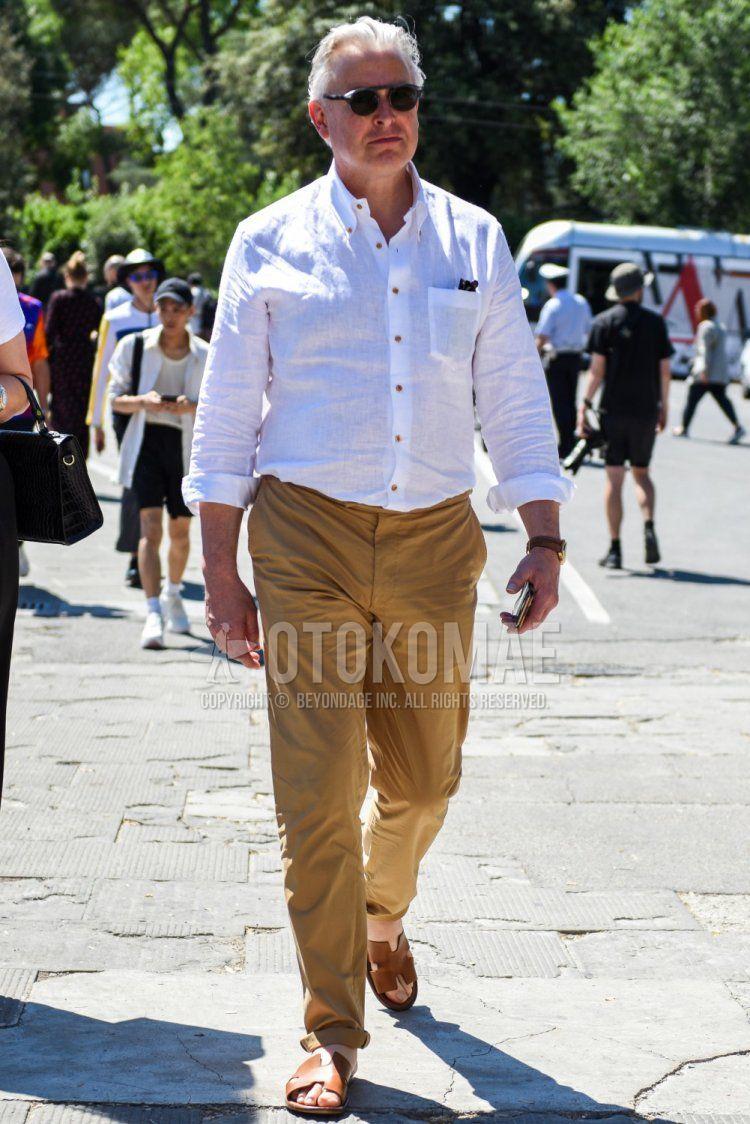 グレー無地のサングラス、リネンの白無地のシャツ、ベージュ無地のチノパン、エルメスのブラウンレザーサンダルを合わせた春夏のメンズコーデ・着こなし。